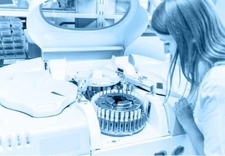 Laborszene mit Blutproben und Zentrifuge und Frau