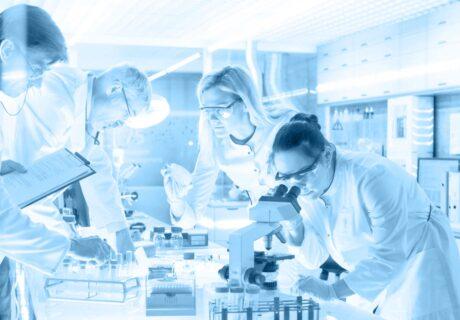 Laborszene Frau sieht durch eine Mikroskop